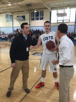 CBA junior forward Pat Andree (center) is congratulated by head coach Geoff Billet (right) and athletic director Vito Chiaravalloti (left) after Andree scores his 1,000th career point.