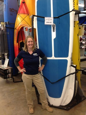 General Manager Roz Clark poses with some of the equipment at West Marine's new Davis Highway superstore.
