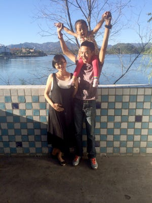 Zhang Xue, left, husband Shi Huili and daughter Shi Yuqi, shown at a suburban Beijing lake in September, will add  to the family this month.