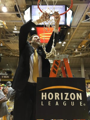 Valparaiso basketball coach Bryce Drew cuts down part of the net following his team's victory in the Horizon League tournament championship game.