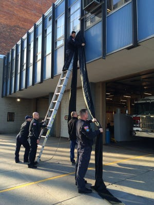Cincinnati firefighters hang a black banner across Station 14 Friday morning in remembrance of Daryl Gordon.