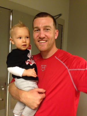 Reds infielder Todd Frazier poses with 1-year-old son Blake after Cincinnati's 5-2 win on Opening Day.