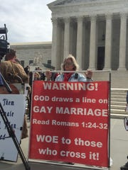 Christine Weick of Grand Rapids holds a sign outside the Supreme Court before oral arguments over gay marriage that include a Michigan case.