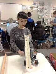 Ben Govaere, 11, a sixth grader at St. Clair Middle School, checks out his team's robot.