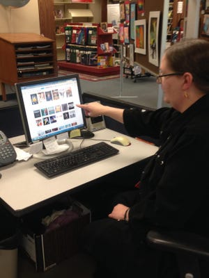Library associate Karen Marks points out a Kurt Cobain documentary that's just one of the hundreds of movies available to Wicomico County library card holders via Hoople Digital.