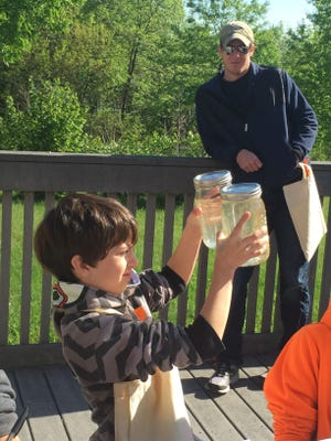 Ethan Harrington examined two jars of fresh water, one from before rainfall and one from after. A fourth-grader at Edgelea, Harrington has been learning about water quality as part of a program run by the Tippecanoe County Partnership for Water Quality.