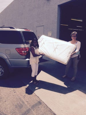 Arizona Helping Hands Service Director Jodelle Doyle and intern Laura Scheel load a crib for a foster family