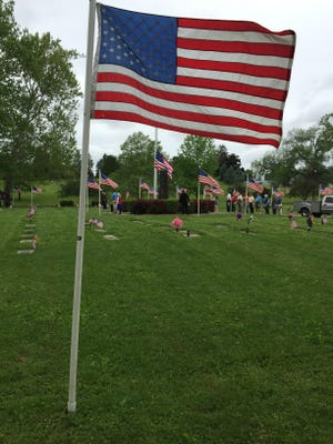 The flag flies during the singing of the national anthem during 2015 Memorial Day services in Richmond.