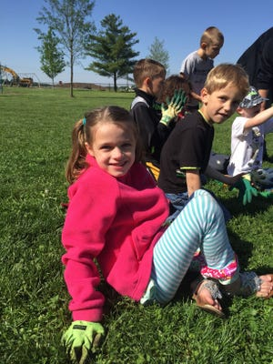 Mintonye students Madelyn LaPlante and Henry Heckathorn, both in kindergarten, sat with their classmates removing gardening gloves. The students spent the morning breaking up soil to prepare the beds for planting.