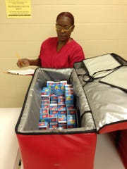 Barbara Cole of Alexandria Middle Magnet School looks over the milk supply at Alexandria's Summer Day Camp on Monday. Food for the camp is coming from the Rapides Parish School District, and Monday's lunch was prepared at Alexandria Middle Magnet School.