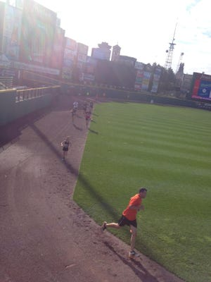 Runners round the warning track at Frontier Field during the Medved 5K to Cure ALS in 2014. Runners finish the race on the field.