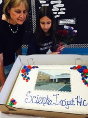 "Library motto winner Lauren Articolo and Moorestown Friends School latin teacher Linda Vizi admire a special cake for her 5th grade Latin class at Moorestown Friends School. Its icing carries her winning Latin phrase ""Scientia Incipit Hic."" The motto, which means ""Knowledge Begins Here,"" will replace a controversial phrase on the outside walls of the new Moorestown Town Hall/Library building."