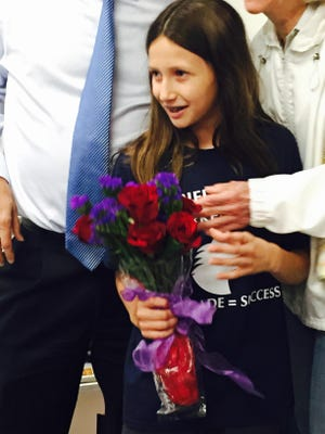 A shy Lauren Articolo of Marlton, a fifth grader at Moorestown Friends School, receives a bouquet at Wednesday's announcement that her Latin motto won a township contest and will be inscribed on the new township library and town hall building. She and the other students in fifth grade Latin class at the school submitted 40 of the 65 entries received by township council and the library trustees.