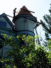 Workers remove shingles from the tower of the Burger home, built in 1894.