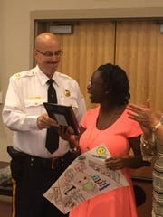 Veterans Memorial Intermediate School eighth-grader Alexsia Gillespie is awarded a Kindle from Vineland Police Captain Tom Ulrich for her second place finish in a poster contest to stop shoplifting.