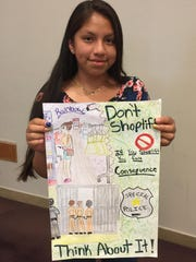 Seventh-grader Evelyn Regino Reyes holds her poster that won first place honors in a contest hosted by the Vineland Police Department to help combat shoplifting.