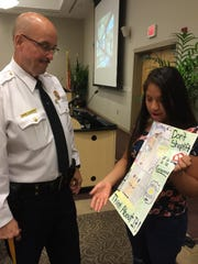 Seventh-grader Evelyn Regino Reyes discusses her poster that won first place honors in a contest to help combat shoplifting with Vineland Police Captain Tom Ulrich.