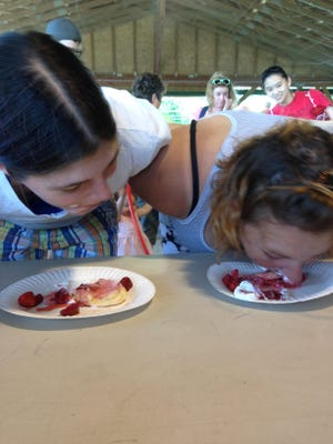 """Tiffany Cochones, left, and Mary Wright, right, of Burlington, compete in a strawberry shortcake-eating contest Saturday at Mazza's Strawberry Festival in Colchester. The women are sisters-in-law who attended the festival with other family members. """"It's awesome,"""" Wright said. """"My mom wanted to bring all the grandkids."""""""