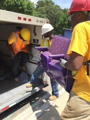 Workers load a pair of seats from Littlejohn Coliseum into Will Mahoney's U-Haul Friday afternoon.