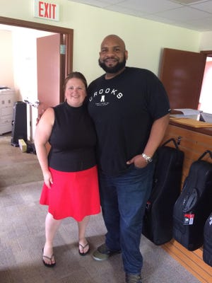 Coles Music Service owner Lauralee Houghton stands with Dave Matthews Band trumpeter Rashawn Ross Friday.