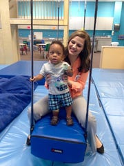 Kingston Cooper, 1, balances on a moving swing with help from speech language pathologist Melissa McTire at the Pediatric Therapy Center of Christus St. Frances Cabrini Hospital on Friday.