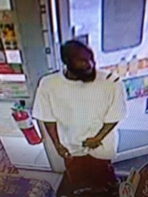 Surveillance images shows a man who entered a 7-Eleven Friday evening and pointed a gun at a store clerk after he was told the bathroom was out of order.