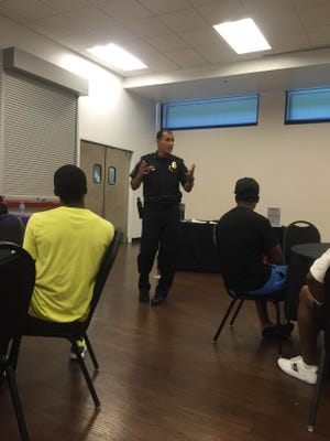 Phoenix police Sgt. Mark Tovar spoke to youths at the Kickstart Mentorship Academy on Saturday, June 27, 2015, about interacting with police officers.
