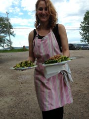 Tessa Hill carries two salads from the food cart to a picnic table at Broken Arrow Café in South Hero.