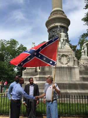 Mike Williams, state adjutant for the Alabama division of the Sons of Confederate Veterans, carries a Confederate battle flag while shaking hands with young men who arrived at the monument to support the removal of the Confederate flags, Wednesday, June 24, 2015, in Montgomery Ala. Williams arrived shortly before to protest the flags' removal. Alabama Gov. Robert Bentley ordered Confederate flags taken down from a monument at the state Capitol. (AP Photo/Martin Swant)