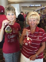Jerill Roberson, left, and Johnnie Stillwell pose with Alabama Christmas ornaments in Hoover, Ala., at SEC Media Days on Wednesday.