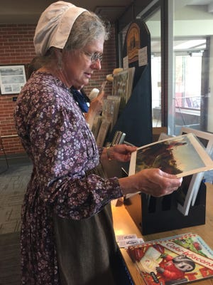 """Kitty Latane admires an original illustration from the """"My First Little House"""" books by Renee Graef. Latane has lived in Pepin, Wisconsin, the birthplace of Laura Ingalls Wilder, for 30 years."""
