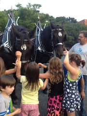 Kids pet the horses at the downtown Wharf parking lot