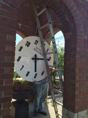 Worker Ricardo Saenz helps lift one of the clocks to the top of the Haslett Commerce Center clocktower Wednesday, July 22, 2015.