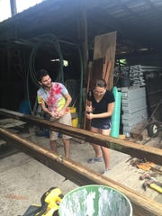 Connor Flanagan, left, and Amanda Shawless work on beams for a new bird cage at Everglades Wonder Gardens.