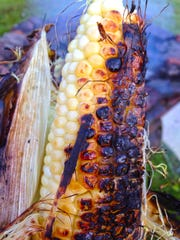 An ear of corn roasted in its husk, after being soaked in water, in a fire pit at a Joe's Pond camp.