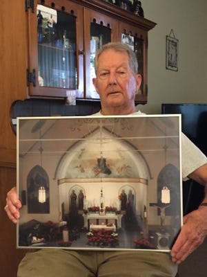Long-time parishioner Bill Kohut holds a photograph of the altar at St. Mary's in Haverstraw village.