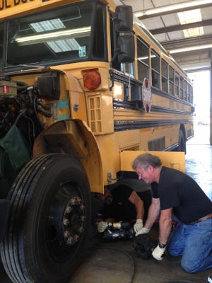 Chris Dauzat gives Wayne Davis a new starter to place in a Rapides Parish school bus on Wednesday. An increase in bus routes this year has maxed out the school district's bus supply, so the district Transportation Department is repairing buses to serve as back-ups in case of breakdowns.