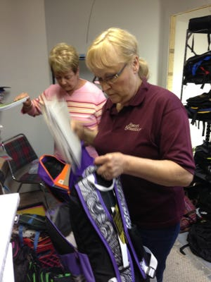 Kari  DeRosa, front, vice president of Holt-based Give-A-Kid Projects, and Sandy Wriggelsworth, secretary, fill backpacks with school supplies Wednesday in the group's warehouse in Delhi Township.