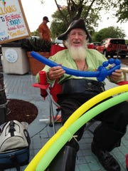 Reggie Clarke of Alabama appears as Capt. Calico Jack at Times Square in Fort Myers Beach, making balloon cutlasses and other balloon shapes in return for donations to an animal refuge.