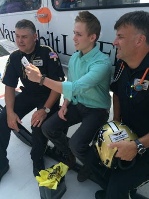 Sam Ray, middle, sits with Vanderbilt LifeFlight pilots Friday, Aug. 14, 2015, at Vanderbilt University Medical Center. Ray used his iPhone's Siri function to call 911 after a jack propping up his truck collapsed, pinning him under the almost 5,000-pound vehicle.
