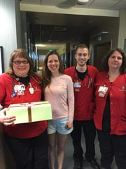 Emily Goertemoeller, second from left, delivered cupcakes to area businesses, such as the oncology staff at IU Health Arnett Hospital, before opening.