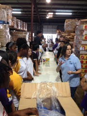 Carol Stafford (right, in blue), volunteer coordinator at the Food Bank of Central Louisiana, tells about 50 Louisiana State University of Alexandria freshmen students what food to pack in backpacks for Rapides Parish students on Friday. The volunteer community service is part of freshman orientation.