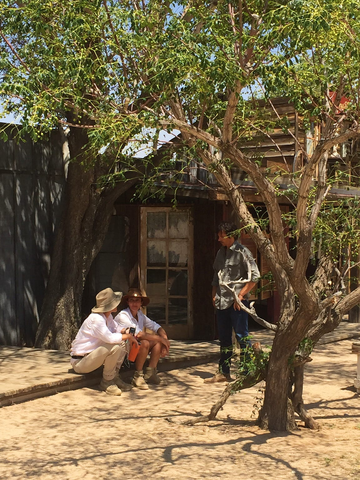 Bell huddles with the actors in the shade between takes.