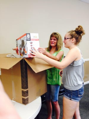 Recently homeless Kathleen Nervosa and teen daughter Spencer open a box from Volunteers of American with dishes, pans and other starter items for their new apartment in Blackwood