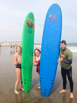 """From left, Michele Aed, Jen Meyer and Summer Surf instructor/owner Mark """"Gilly"""" Gilmartin."""