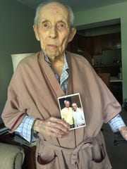 Ron Gilbert, 103, holds a photograph of him with Bobby Plump. Gilbert, who worked for the Star in the 1940s and the AP from about 1944-'67, was sitting behind the Milan bench for the 1954 Indiana state title game that Plump won in the final seconds. Gilbert lives on Indianapolis' Northside.