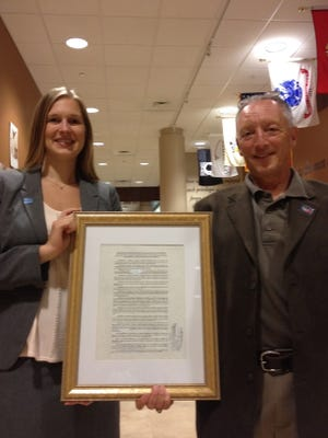 Amy Jesse, public policy coordinator for the National Humane Society, and community activist Alan Braslow pose with a framed copy of the new ordinance.