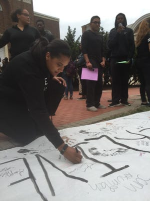 Tanya Jankowski signs her name on a banner declaring #BlackLivesMatter on the University of Delaware campus, where a Fox News pundit was set to speak on Monday night.