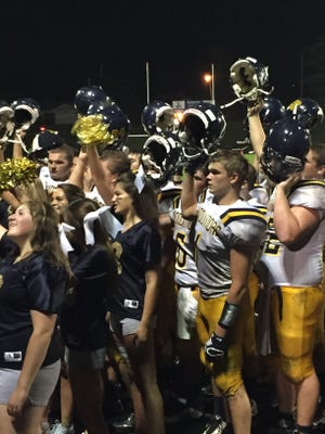 Conner Haas, front, hold his helmet up with teammates and Woodmore students after a victory this season.