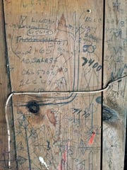 Doodles and phone numbers written in pencil half a century ago or earlier cover a section of the wall inside Loie Hayward's 1917 barn north of Dysart.